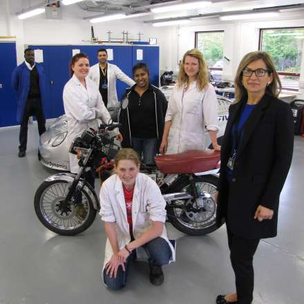 Students and staff with vehicles in the automotive lab