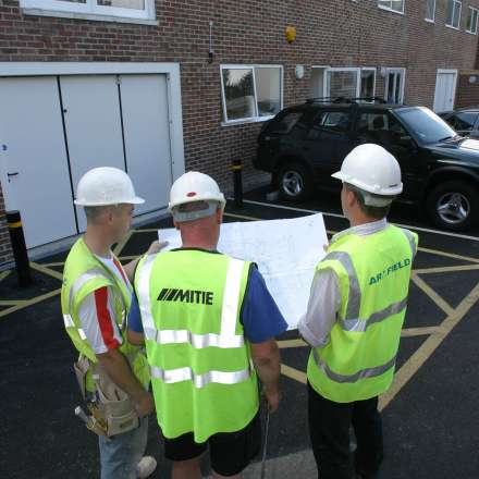 Surveying student with course leaders inspecting plans