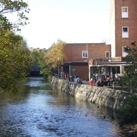Students gathering outside the Students' Union bar by the Hogsmill River