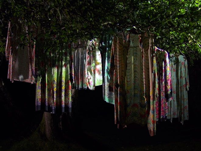 Still of colourful smocks hanging in a tree from Florence Kennard\'s film, Norma\'s Colours.