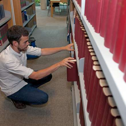 Student choosing books in the law section of the LRC