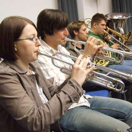 Group of music students playing brass instruments at orchestra practice