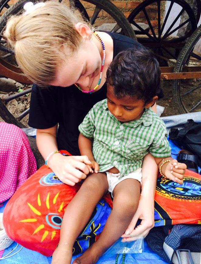 Student volunteer Catherine Green with the young son of one of the families living in a Chennai beach slum.