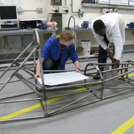 Reviewing a motorcar frame in the automotive engineering lab