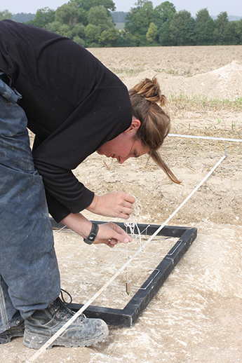Dr Helen Wickstead examines part of the excavation site at Damerham, near Stonehenge.