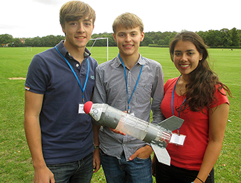 Course participants, from left to right, Matt Harvey (Newcastle-Under-Lyne School), James Tunsley (Perse School) and Alexandra Marland (Tormead Senior School) show off the rocket they created as part of the programme.