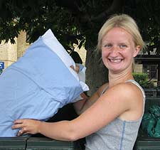 Student Daisy Addison puts a pillow into one of the collection bins