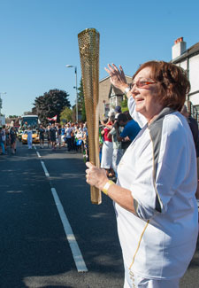 Margaret Loveridge prepares to receive the flame from Reda Vida Gani in front of hundreds of spectators on Penrhyn Road.